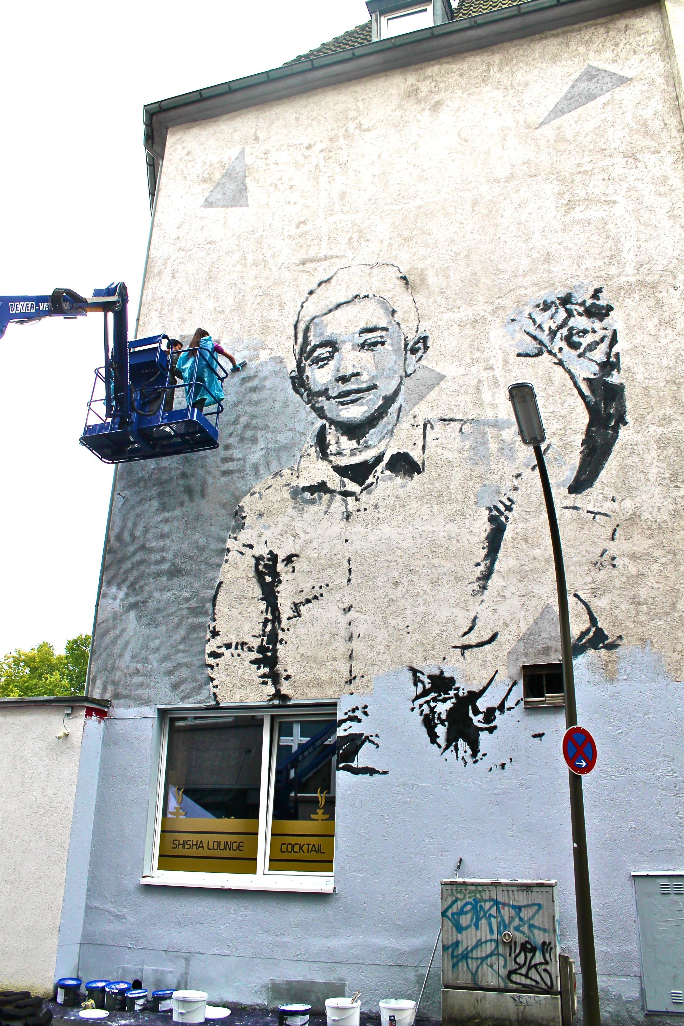 Über mehrere Tage hinweg entsteht im Rahmen des HUNA/K Festivals in der Münsterstraße dieses große Wandgemälde.